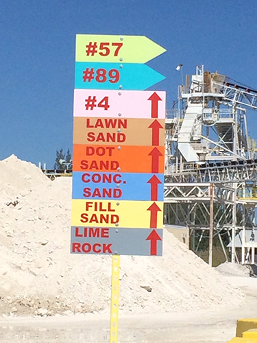Color-coded signs, above, help customers find their way to specific stockpiles at Cemex's Krome Quarry, while, below, a haul truck loads material into a crusher.
