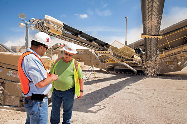Adam Smith (left), service manager for Texas Bearing Co., talks with Chris Duplooy, plant foreman for CSA Materials.