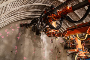 An underground drill jumbo is an example of percussive drilling. The first mechanized percussive drill was invented in 1844 using compressed air to apply the percussive load to strike the drill. Photo: AcademyBlasting.com